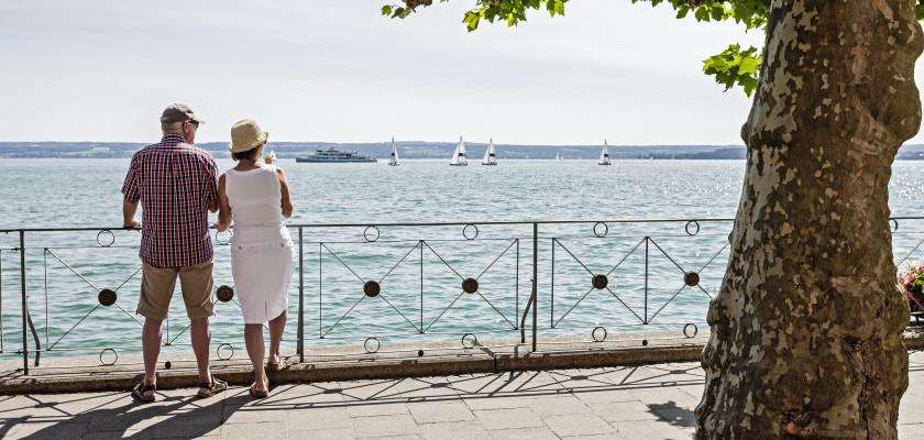 Blick auf zwei Menschen. Sie stehen mit dem Rücken zum Betrachter und lehnen an das Geländer der Seepromenade. Im Hintergrund leuchtete blau der Bodensee.