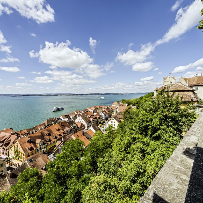 Blick von oben auf die Häuser der Unterstadt. Im Hintergrund ist blau der Bodensee sowie blauer Himmel.