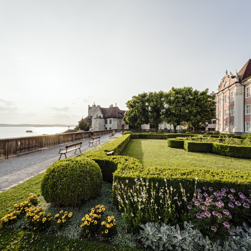 Blick entlang der Schlossterrasse. Rechts das rosafarbene Neue Schloss Meersburg. Mittig der kleine Park des Schlosses. Links liegt der Bodensee.