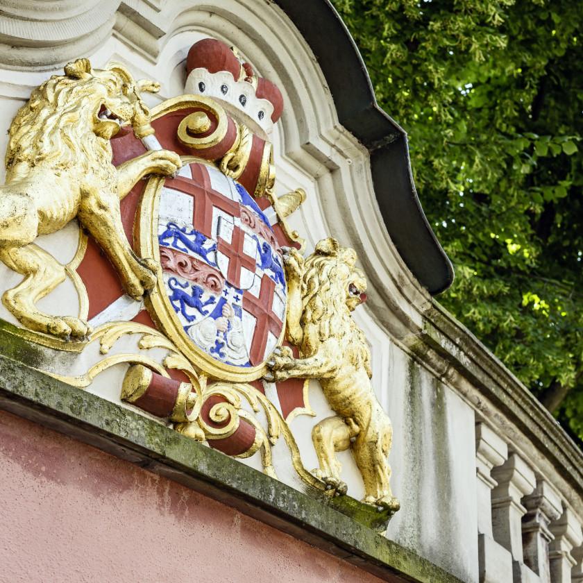 Blick auf ein Wappen des Neuen Schlosses. Das Wappen besteht aus den Farben rot, blau und weiß. Es ist umrahmt von zwei goldenen Figuren.