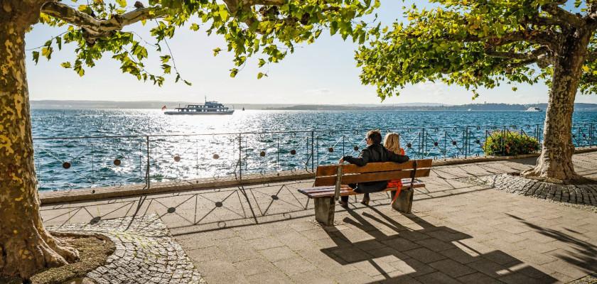 Blick auf ein Paar. Dieses sitzt mit dem Rücken zum Betrachter auf einer Bank an der Promenade und betrachtet den Bodensee.