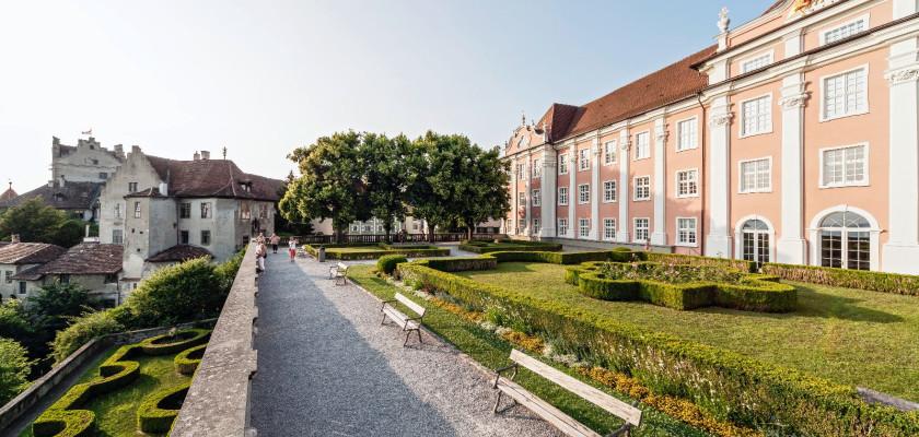 Sicht entlang der Schlossterrasse. Rechts das rosafarbene Neue Schloss. Links die steinerne Brüstung. Im Hintergrund die Burg Meersburg.