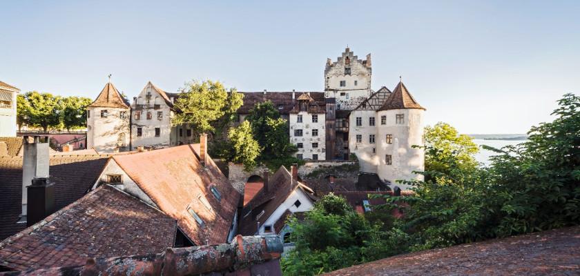 Abbild der vollen Länge der Burg Meersburg. Neben der Burg ragen einige Häuser der Altstadt empor.