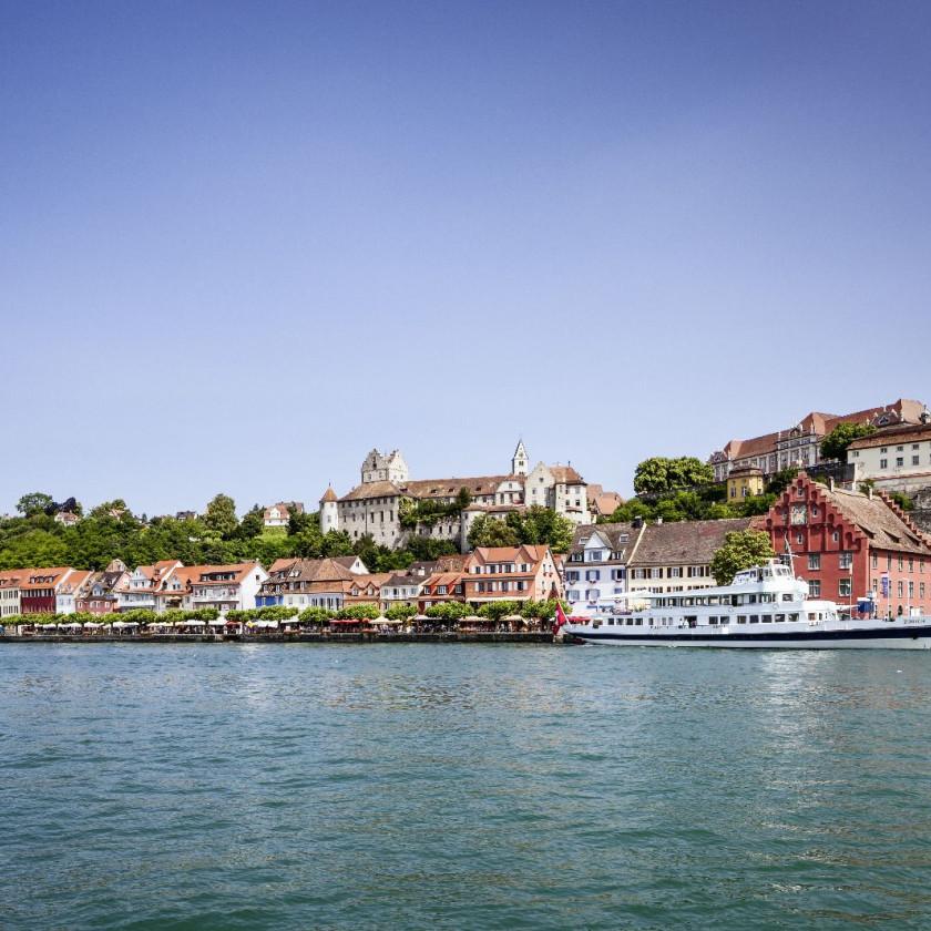 Abbild des Stadtpanoramas von Meersburg vom Bodensee aus. Vor der Promenade fährt ein weißes Personenschiff vorbei.