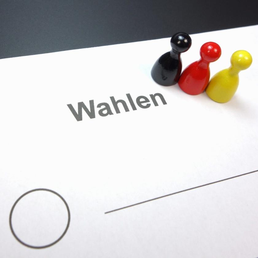 Dokument mit der Aufschrift Wahlen. Darauf stehend Spielfiguren in schwarz, rot und gelb.
